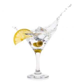 Мартини всплеск с лимонным кубиком льда и зелеными оливками в коктейле