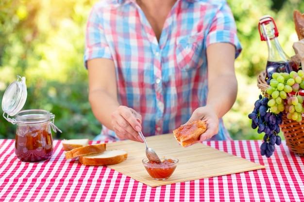 格子縞のシャツを着た女性がスプーンでパンにジャムを塗る