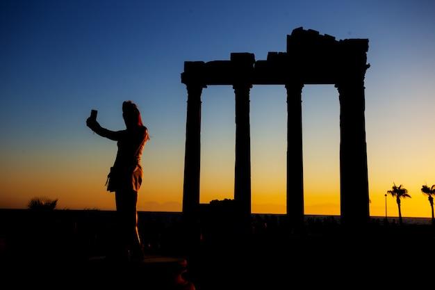 Силуэт девушки, делающей селфи в храме аполлона на закате