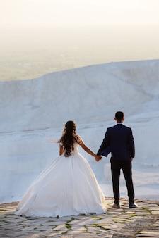 Молодая пара свадьбы стоит над скалой, держась за руки и смотрит вдаль