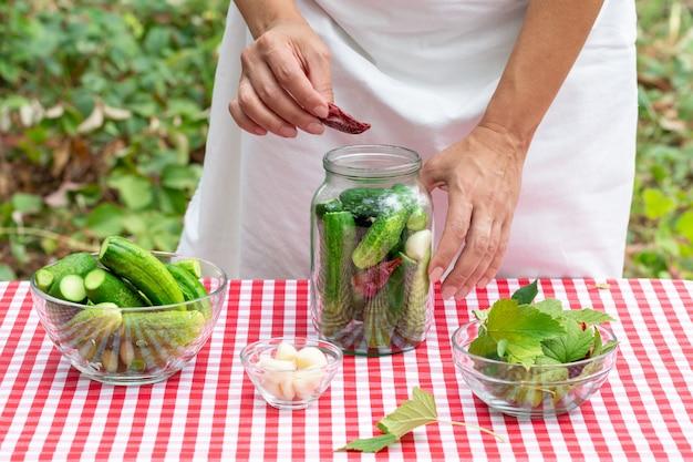 女性料理人は保存のためにキュウリとガラスの瓶に赤唐辛子を入れます