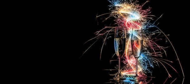 Бокалы с шампанским в ярком свете разноцветной бенгальской свечи
