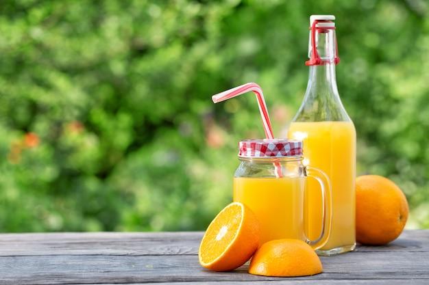 Свежий апельсиновый сок и нарезанные апельсины на деревянном столе