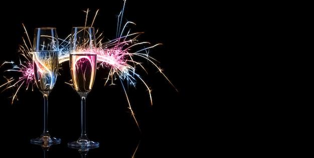 Два высоких бокала шампанского в свете бенгальских огней