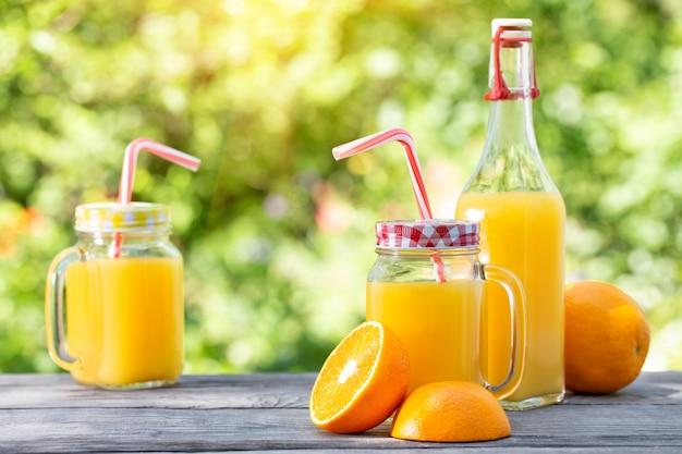Апельсиновый сок и нарезанные апельсины на деревянном столе