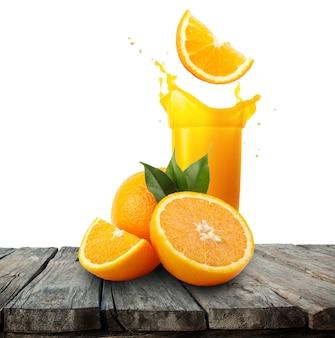 Стакан апельсинового сока с всплеск и апельсины на деревянный стол
