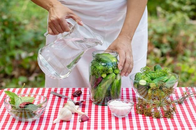 女性の手は保存のためにデカンタからキュウリの瓶に水を注ぐ