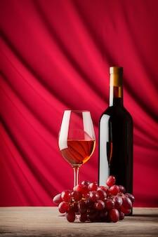 ボトルと緋色のサテンの背景に赤ワインのガラス