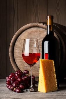 ボトルと赤ワインのグラスとチーズとブドウ