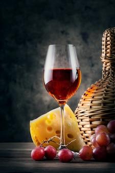 ブドウと枝編み細工品のボトルと赤ワインのガラス