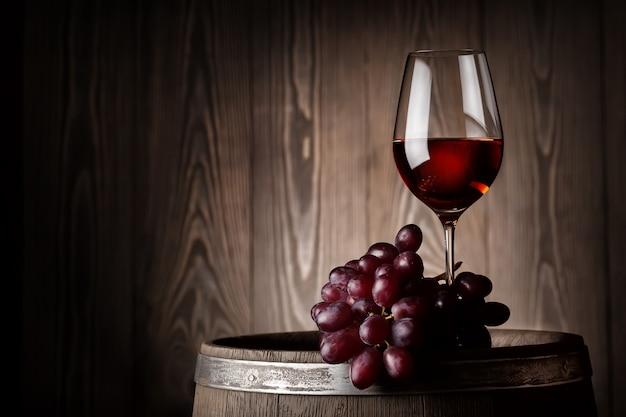 木製の樽のブドウと赤ワインのガラス