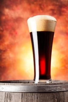 泡と木製の樽で黒ビールの背の高いグラス