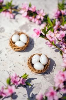 Цветет розовыми и яйцами в гнезде и копирует пространство.