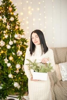クリスマスツリーの若い女性。ニットドレスのモミの枝を持つ女性。