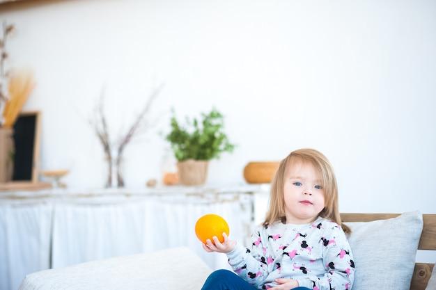 Смешная девчонка на диване. счастливый ребенок дома на кухне в деревенском стиле.