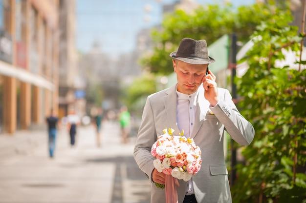Мужчина в костюме и шляпе на улице с букетом. парень, цветы, лето, ожидание.