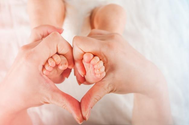 手のクローズアップで新生児の足。赤ちゃんの足とコピースペース。乳児ケアと疝痛