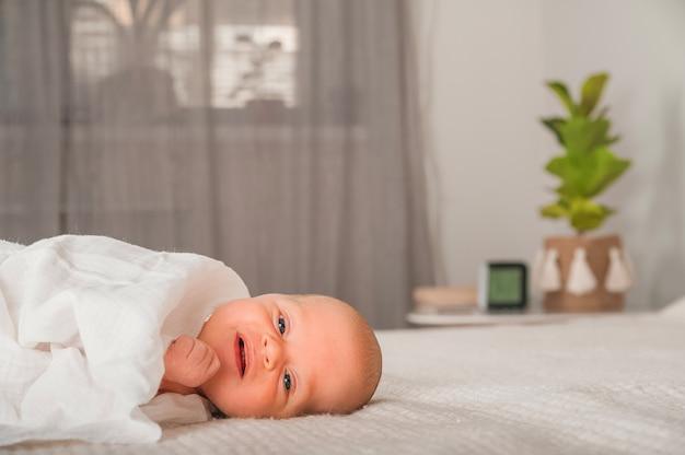 ベッドの上の新生児。新生児の赤ちゃんの笑顔と疝痛。