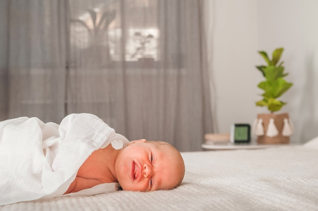 ベッドの上の新生児。泣いて、叫んで赤ちゃんをクローズアップし、スペースをコピーします。新生児の赤ちゃんの笑顔と疝痛。