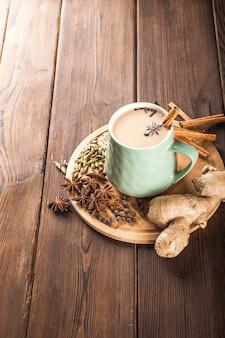 暗い背景に木の板の粘土カップ。マサラティーのカップ。スパイスクローブ、フェンネル、シナモン、カルダモン、ミルク。