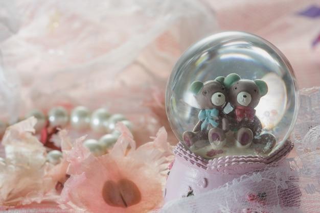 Мишки тедди в снежном шаре на розовой ткани с жемчужным ожерельем