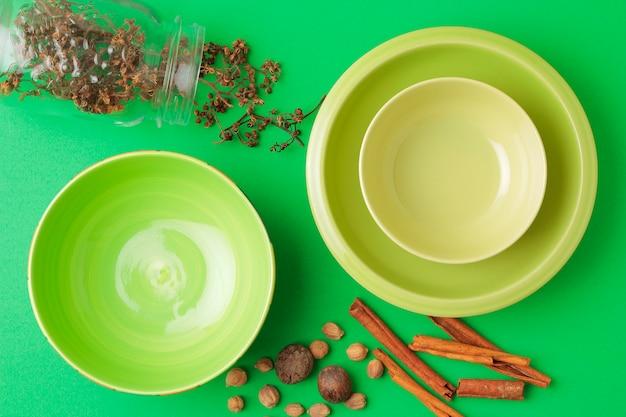 緑のボウルと緑のテーブルの上のスパイス。