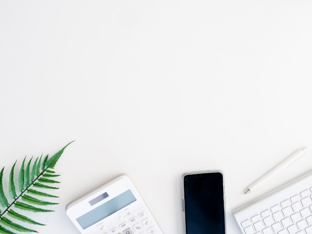 電卓、ノートブック、プラスチック工場、スマートフォン、白い背景、グラフィックデザイナー、創造的なデザイナーコンセプトのキーボードとオフィスデスクテーブルのトップビュー。