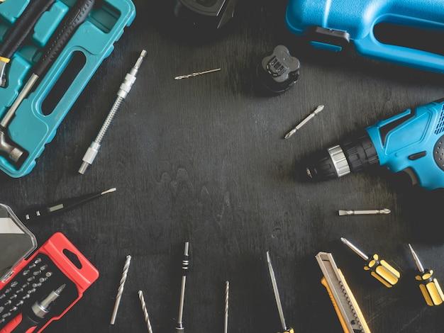 Вид сверху концепции строительных инструментов с набором сверл, молотком, отверткой и набором инструментов на черном деревянном фоне.