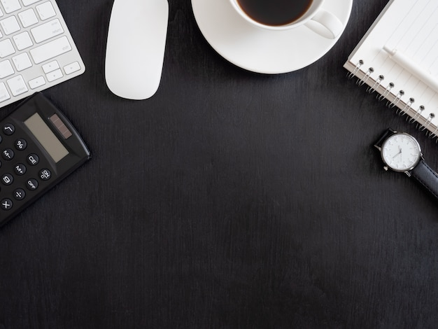 Взгляд сверху таблицы стола офиса с тетрадью, пластичным заводом, калькулятором и клавиатурой на черной предпосылке, график-дизайнером, концепцией творческого дизайнера.