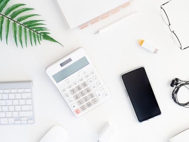 電卓、ノートブック、プラスチック工場、スマートフォン、キーボードとオフィスデスクテーブルのトップビュー