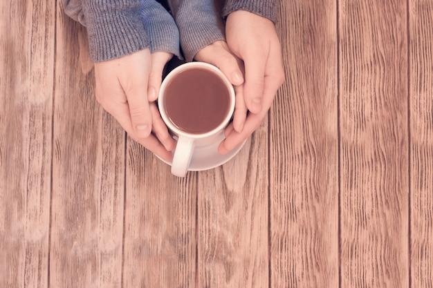 木製のテーブルにお茶の熱いカップを保持している女性とメンズの手