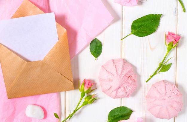 手紙、封筒、白い背景の上のエコ紙のプレゼント。結婚式招待状またはピンクのバラとラブレター。