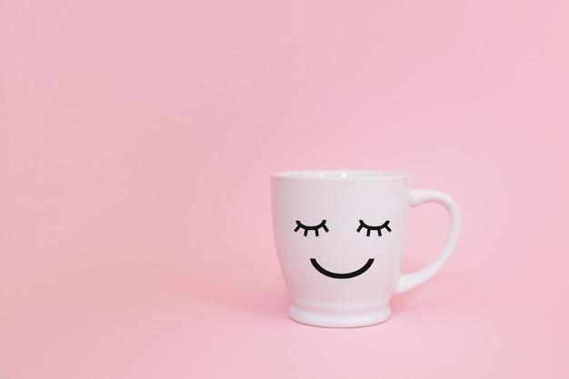 Счастливое слово пятницы. чашка кофе на розовом фоне с улыбкой лицом на кружку.