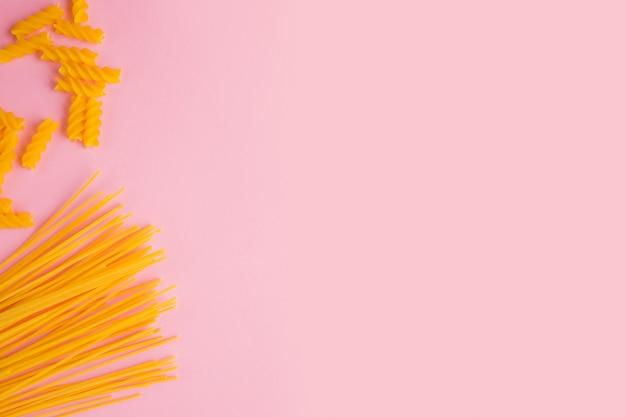 Итальянская паста. желтые длинные спагетти и макароны на розовом фоне.