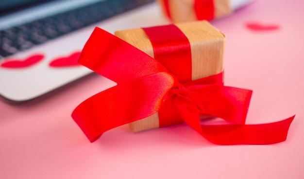 赤いハート、ラップトップとバレンタインの背景。バレンタインの日グリーティングカード。女性の職場。上面図