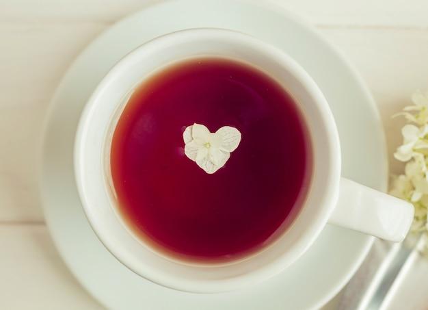 白い背景の上の本の上にお茶のカップが立っています。ハート形の花。朝のロマンチックな朝食。