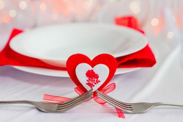 バレンタインデーのロマンチックなディナー。明るい背景にフォークと白いプレートと心