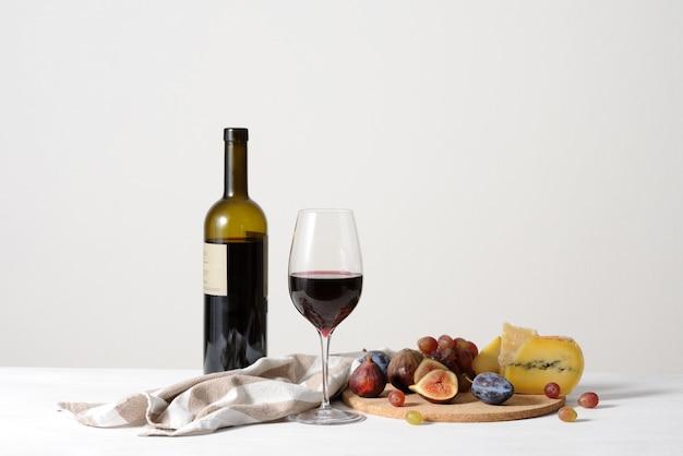 赤ワイン、チーズ、フルーツの背景のある静物