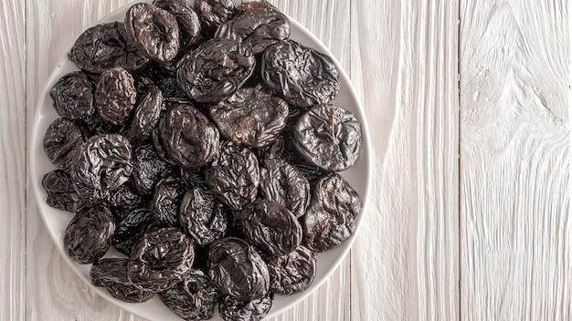 健康的な食事の材料である新鮮なプルーン。木製の素朴なテーブルに白いセラミックプレートで梅を乾燥させます。