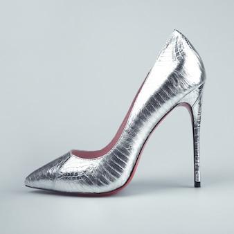 灰色の背景に女性の銀の靴