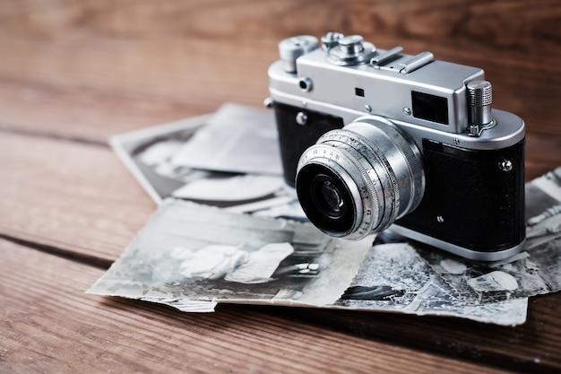 木製の背景にアンティークの写真とビンテージ写真カメラ。