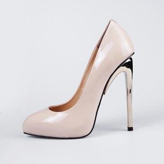 Пара бежевых женских туфель на высоком каблуке на белом