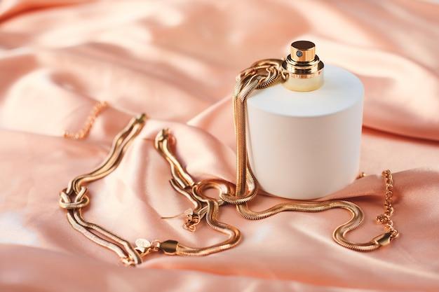 ピンクの背景の金のネックレスと香水瓶