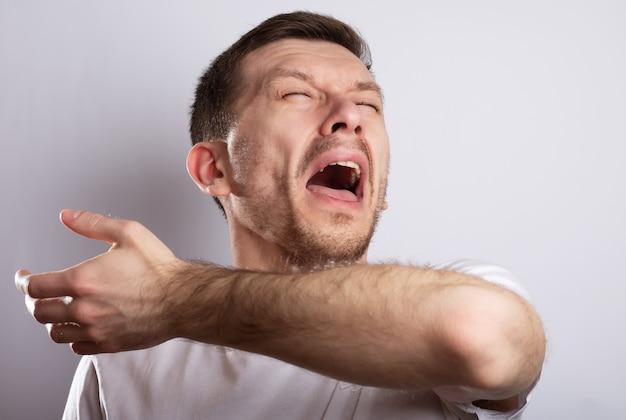 Больной человек чихает на локте