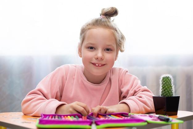 Девочки делают школьные уроки на дому.