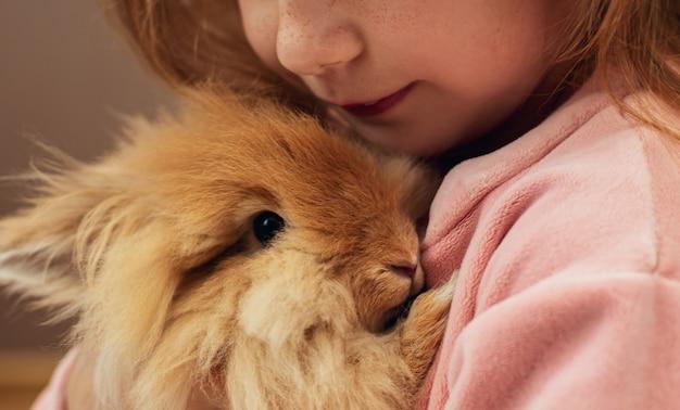 Маленькая девочка обнимает кролика