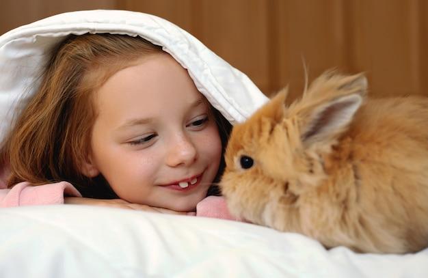 Рыжая девушка играет с красным кроликом