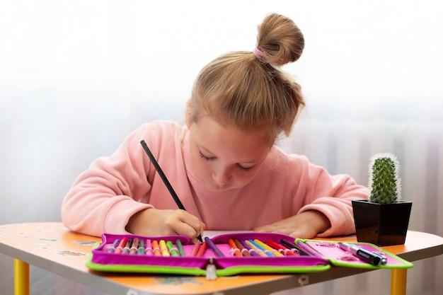 Ребенка девушка делает школьные уроки на дому.