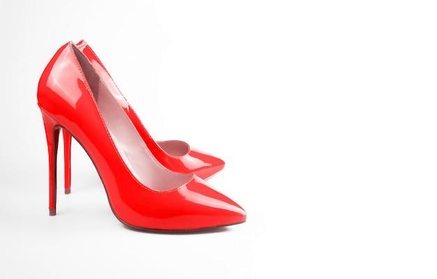 Женские красные туфли на белой поверхности