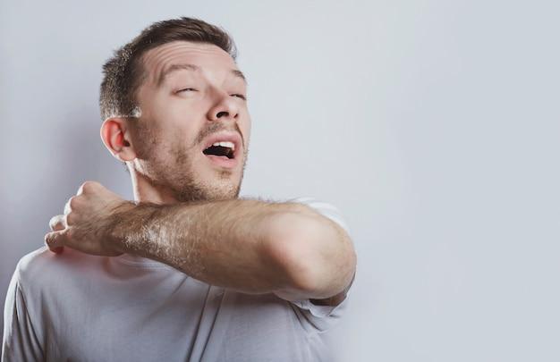 Человек чихает локтем